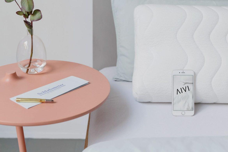 AIVI Soundkissen im Bett mit einem Nachttisch daneben