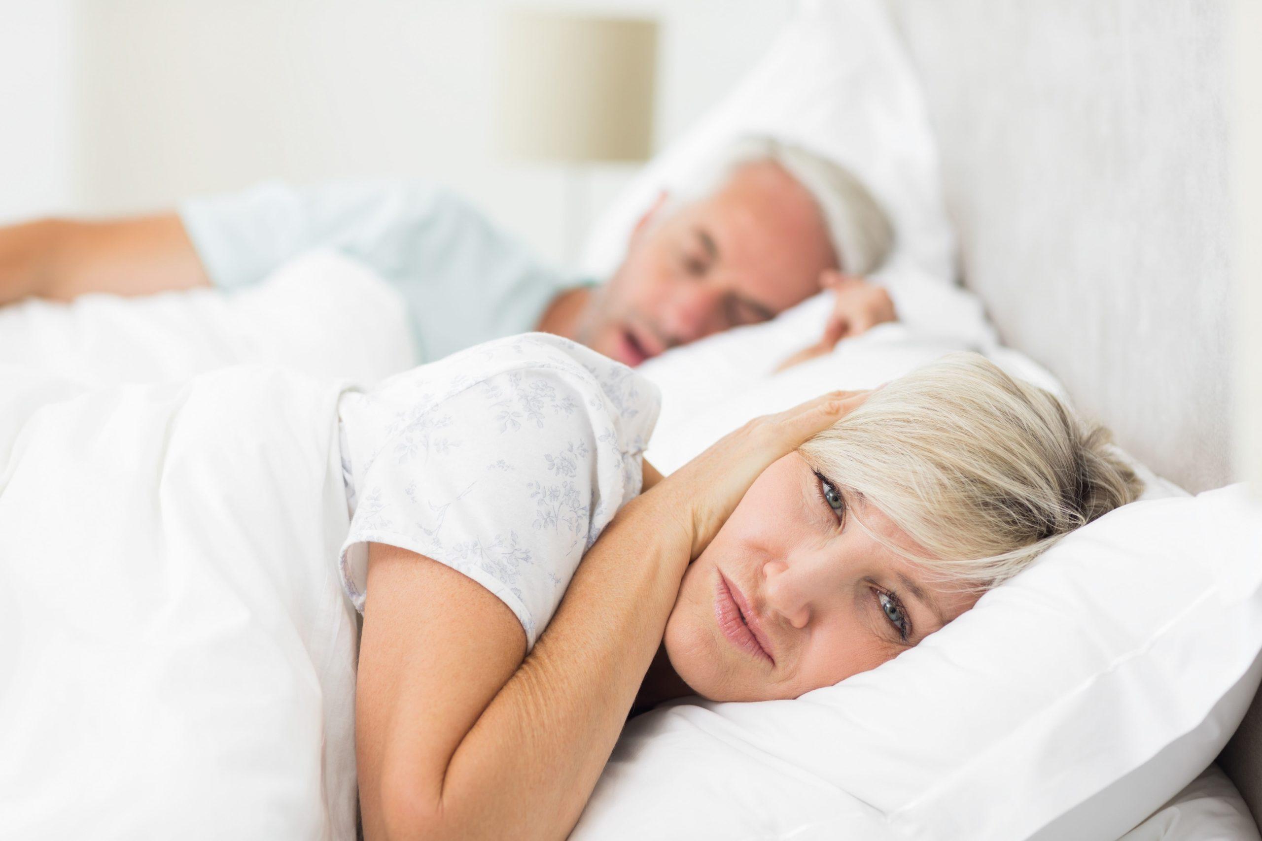 Frau hält sich im Bett die Ohren zu, weil sie das laute Schnarchen stört