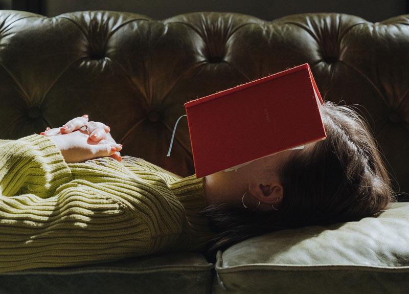 Frau liegt auf lederner Couch mit Buch auf dem Gesicht